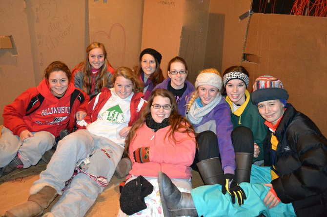 Baker High School students (from left) Kirby Socker, Elizabeth Wisely, Sarah Dugan, Grace Santoro, Sarah Karl, Christine Linnenbach, Emily Soeder, Melissa Voyer and Gretchen Grage get cozy in their cardboard box. The girls spent the night in their makeshift shelter to help raise awareness about the Central New York homeless population and to raise money for the Rescue Mission.
