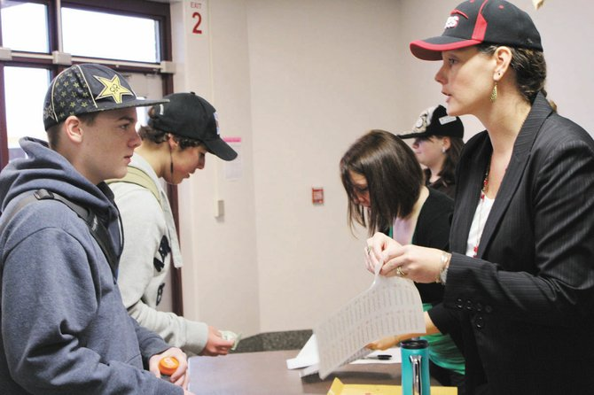 Jennifer AuClair, a teacher at Durgee Junior High School, gives a student a sticker to place on his hat, indicating he donated to the ninth grade's Hurricane Sandy relief efforts fundraiser. For a $1 donation students received a sticker, allowing them to wear hats in school for the day. Hats are not normally allowed in Baldwinsville's schools. The ninth grade raised $450.