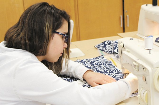Allexia Kimball, a sixth-grader at Ray Middle School, uses the sewing machine to make a walker bag in her family and consumer sciences class. Sixth-graders made walker bags to donate to local hospitals and nursing homes.