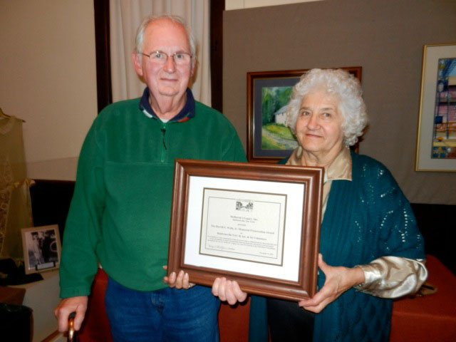 Ben and Nicole Schlater accept the Burrill E. Wells, Jr. Historic Preservation Award for the restoration of their historic home at 61 Oswego St., which was the former Payne Bigelow House built in 1847.