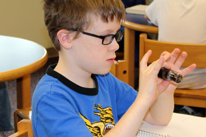 Russel Meeker, a fifth-grader at Palmer Elementary School, examines a vacuum tube used in radios from the 1920s to the 1960s.