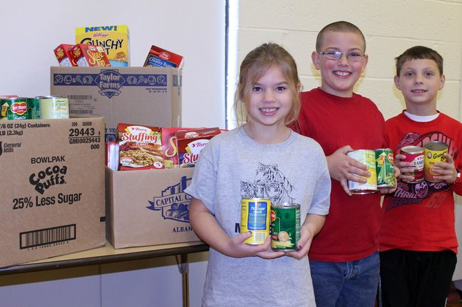 (From left) Morgan Provo, Hunter Kent and Toby McIntyre help to pack up food items that Elden Elementary School collected for the Baldwinsville Volunteer Center for Thanksgiving. The school collected several hundred items such as stuffing and canned vegetables.