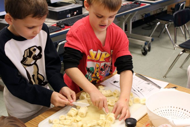 Declan Downes, left, and classmate Xander Mills cut up bananas for fruit salad for Palmer Elementary School's kindergarten harvest feast, which they held before Thanksgiving break.