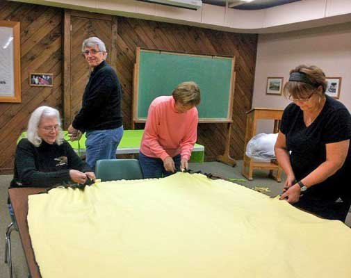 A  team of about 16 Schroon Lake-area women have worked together on two separate days to make special tie-knot fleece blankets to send to local servicemen and women overseas during the holiday season.   From left are Diane Leah, Joe Avignone, Kathy McCoy and Betsi Calhoun.