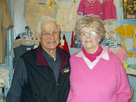 Lorraine Erikson, wearing one of her own sweaters, is joined by her husband, Tom, in Lorraine's Boutique at The Marketplace in Schroon Lake. The shop sells Erikson's knitted clothing as well as a variety of other items.