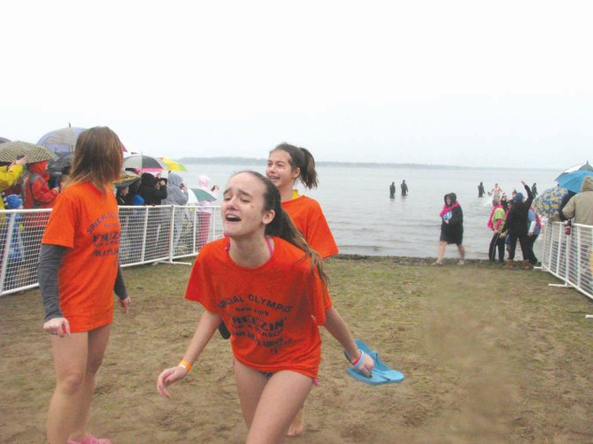 Ashley Scott, center, and other members of Brooke's Splash Puppies emerge from Oneida Lake Sunday morning after taking the Polar Plunge for Special Olympics New York. The team raised about $1,300 for the organization in honor of Special Olympian Brooke Jones (not pictured), who also took the plunge.