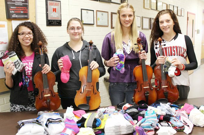 (From left) Della Patterson, Gwen Parks, Morgan Starczewski and Emily Buis, members of Baker High School's orchestra, display socks collected from the entire orchestra in a drive they coordinated.
