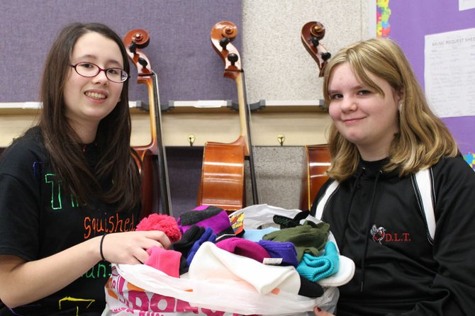 Karin Walker, left, and Mindy Striep count donations from a hat, glove and mitten drive orchestra students at Durgee Junior High School recently collected for the Baldwinsville Christmas Bureau to help keep community members warm this winter.