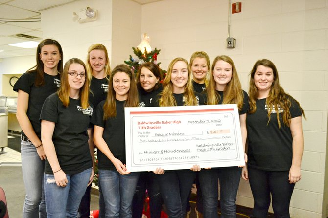 Baker High School juniors (from left) Melissa Voyer, Sarah Karl, Emily Soeder, Kirby Socker, Grace Santoro, Liz Wisely, Gretchen Grage, Sarah Dugan and Chrissy Linnenbach raised more than $4,000 for the Rescue Mission and presented the organization with a check during Channel 9's Movie With a Mission fundraiser on Dec. 2.