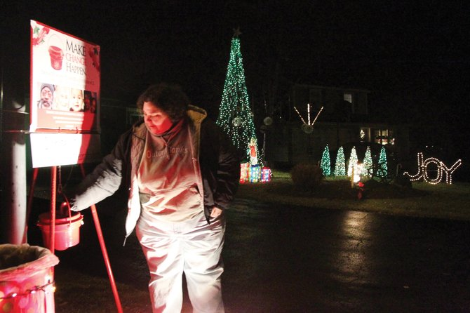 Sue Fritzen of Clay makes a Salvation Army Kettle donation Friday at the Hussak family light show in Liverpool.