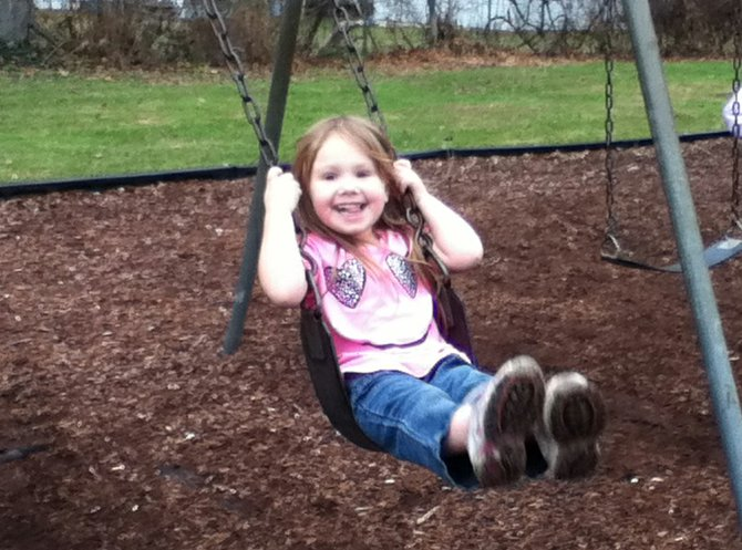 Lillian Jean Benson, 4, of Baldwinsville, enjoys swinging at McHarrie Park last Tuesday when temperatures reached the 70s.