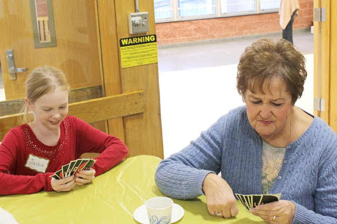 Fifth-grader Jackie Boutilier and Baldwinsville resident Nancy Fletcher play Uno in McNamara Elementary School's cafeteria. The school's student council hosted its first intergenerational activity on Nov. 30.