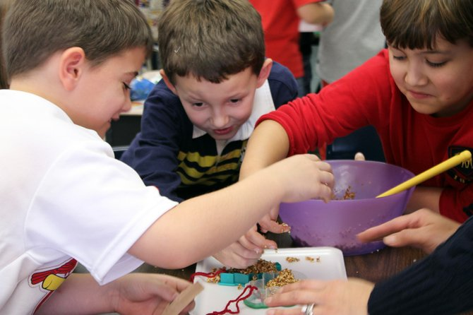 Third-graders (from left) Emmett Bauer Rick Warner, and Harrison Meyers make bird seed ornaments for Syracuse Home.