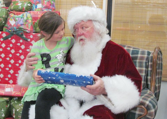 Ariana Davis, 7, visits with Santa Claus during his visit to PEACE, Inc. last Thursday. Davis is a second grader at McNamara Elementary School.