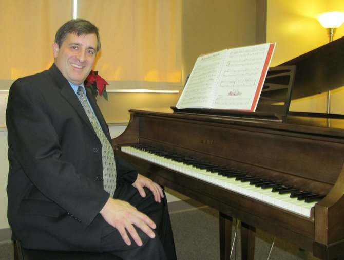 John Damiano sits at the grand piano located in the Baldwinsville School of Music, which opened its doors to the musical community this fall.