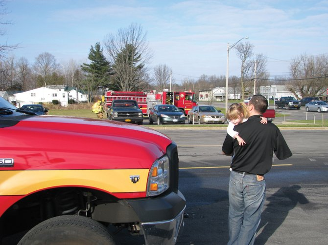 Former Oneida Fire Department firefighter Mitch Dryer, who was severely burned in a 2007 fire, and his daughter Emeri, 2, watch the trucks from Moyers Corners Fire Department as they head out on a call. The Dryers were at the MCFD station for the Burn Foundation of CNY's annual holiday party on Dec. 15.