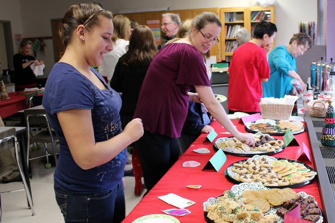 Morgan Cox, left, a student at Durgee Junior High School, invites math teacher Colleen Goss to help herself to all the treats the life skills class prepared for Durgee's staff members.