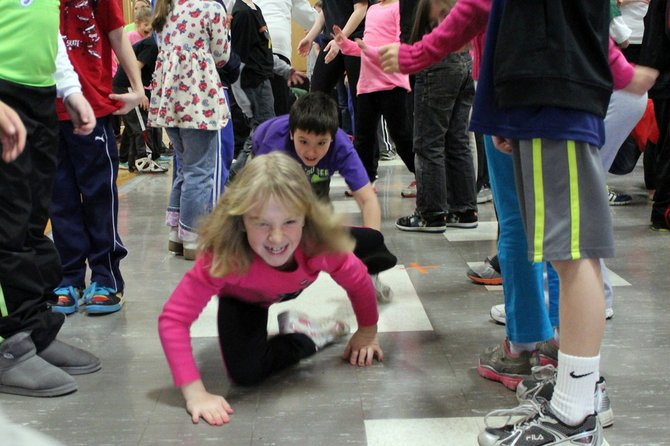 Audrey Benton and her classmate Corbin Haney crawl on the gym floor at Palmer Elementary School during a school-wide fitness activity on wellness day.