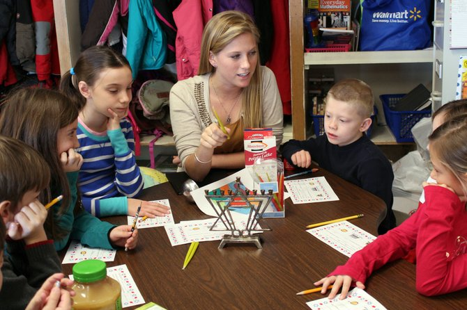 During a cultural lesson, Abigail Sayler, a teacher at Palmer Elementary School, discusses Hanukkah and the significance of lighting the menorah to celebrate the holiday. Sitting around the table are third-graders (from left) Ricky Howard, Emily Forman, Sarah LeMay, Frankie Mazzye and Talia Cusumano.