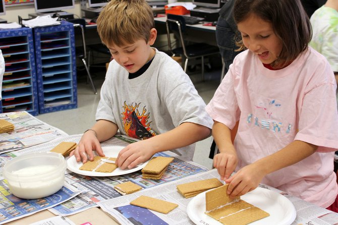 Liam Rausa, left, and Jenna Waclawski, third-graders at Palmer Elementary School, construct gingerbread houses before the holiday break.