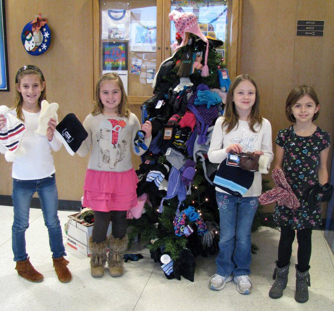 Palmer Elementary School second-graders (from left) Madison MacArther, Mikayla DeCesare, Adisson Lauer and Lily Rine stand in front of the school's hat and mitten tree, which is decorated with the many mittens, hats and gloves the school collected for the Baldwinsville Christmas Bureau.
