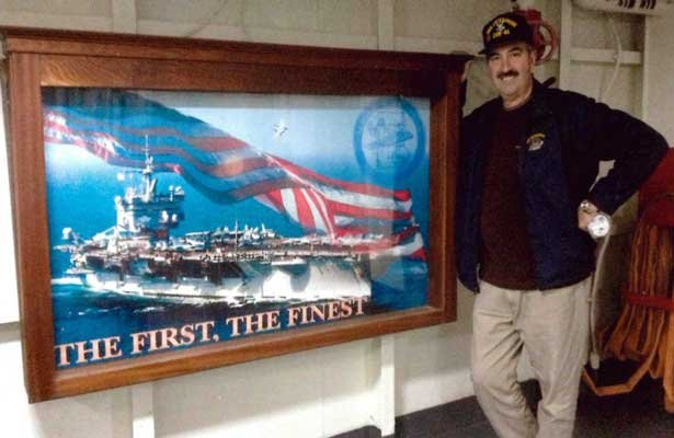 Richard Morgan stands next to a picture of the USS Enterprise.