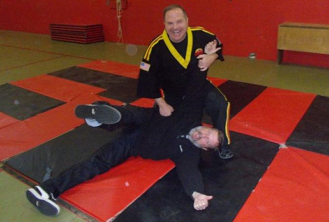 Shihan John Annable, top, puts Baldwinsville Christian Academy Principal Ric Auwarter in a basic karate move.