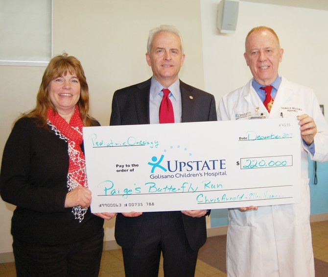 Ellen Yeomans and Chris Arnold present Dr. Welch, professor and chair of Pediatrics at Upstate Medical University, with a $220,000 check for Golisano Children's Hospital. Yeomans and Arnold represent Paige's Butterfly Run, which raised a record amount for the hospital this year. The event is named after Yeomans and Arnold's daughter, Paige, who died after battling leukemia. She was a first grade student at Palmer Elementary School.