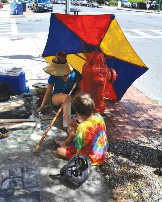 Working on her sidewalk art in August at the Syracuse New Times contest, Elisabeth Holmes explains chalk technique to Benjamin Smith. 