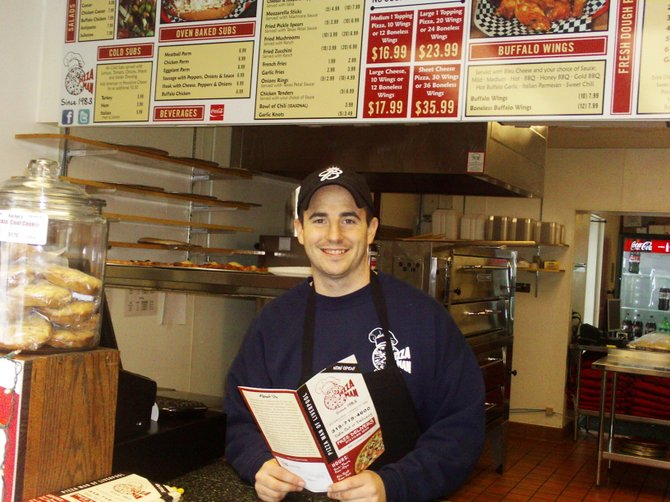 Luke Delia poses inside the new Pizza Man location in Liverpool.
