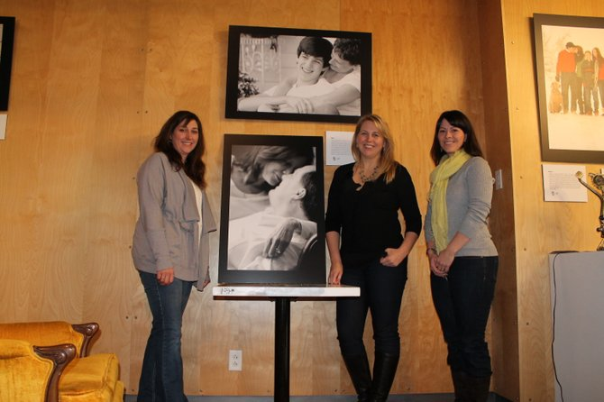 From left, Kristin Atkinson, Tara Polcaro and Kristin Johnson pose with two of their favorite photos on display at The Red House. The three women founded The Molly Project, which provides free photography sessions to women affected by cancer.