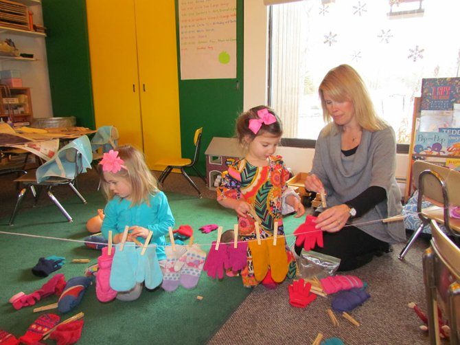 Mrs. Jennifer Jerome works on a mitten matching activity with 3-year-olds Mallory and Reese.