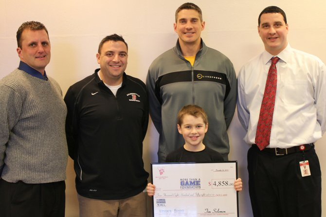 Parker Hysick, a second-grader at Palmer Elementary School, presents Anthony Richmond, left, of the More Than a Game Foundation with a check for $4,858 for the Golisano Children's Hospital.