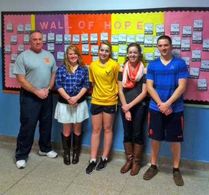 Pictured are Coach John Reynolds, Chelsea Walters, Kaylyn Bennett, Colleen Pine and Matt Moore in front of the Indian Lake Central School Wall of Hope, which identifies the names of contributors and names of people who had contributed money for Indian Lake.  Similar cards were displayed at Long Lake Central School.