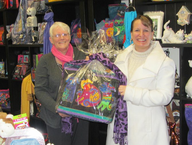 Barb Donaghey, of The Nantucket Cat, proudly presents Karen Young, of Cicero, with a Laurel Burch purse and accessories, which she won during the holiday event, Au Chocolat in Baldwinsville.