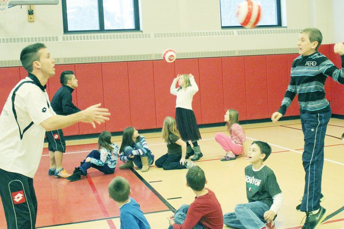 Michael Corsoneti, a student at Elden Elementary School, gets ready to head the soccer ball thrown to him by Nate Bourdeau, a member of the Syracuse Silver Knights indoor pro-soccer team.