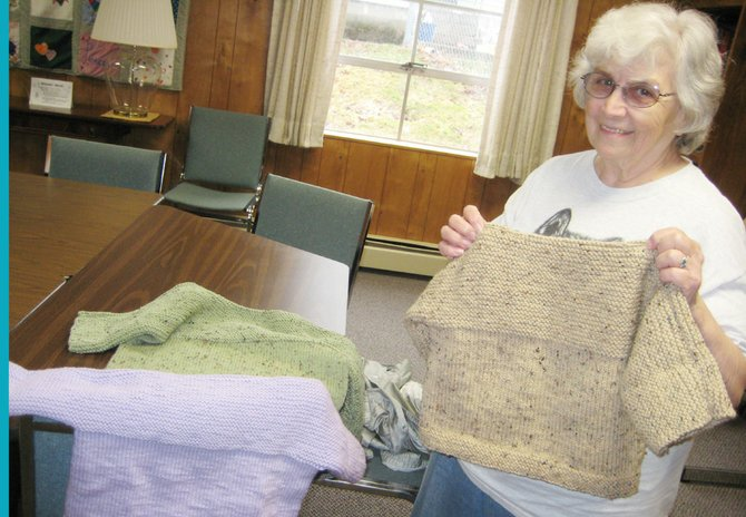 Connie Cuddy displays one of the many sweaters she has knitted for World Vision. Products of her hobby are distributed to children in poverty around the world through the First Presbyterian Church in Baldwinsville.
