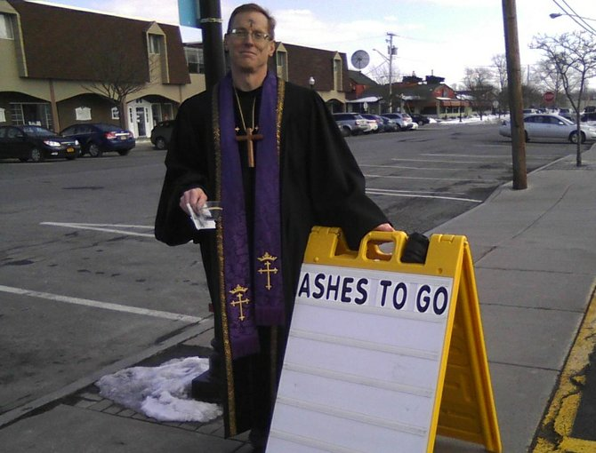 Rev. Garrett Anderson, pastor of Liverpool First Presbyterian Church, provides Ash Wednesday services outside Nichols in the village.