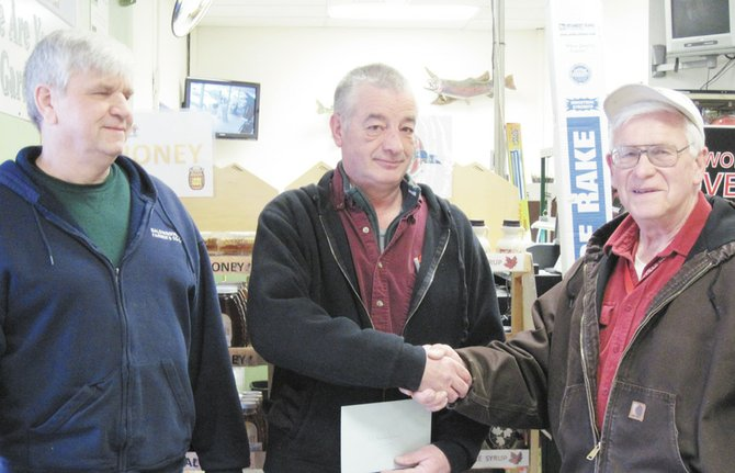 Manager of the Baldwinsville Farmers Co-op, Dennis Gawarecki, left, and president of the Baldwinsville Farmers Cooperative Association, Harold Crandon, right, congratulate Al Huntington for his recognition by the organization, which acknowledged 40 years of dedicated service by Huntington to the Farmers Co-op.