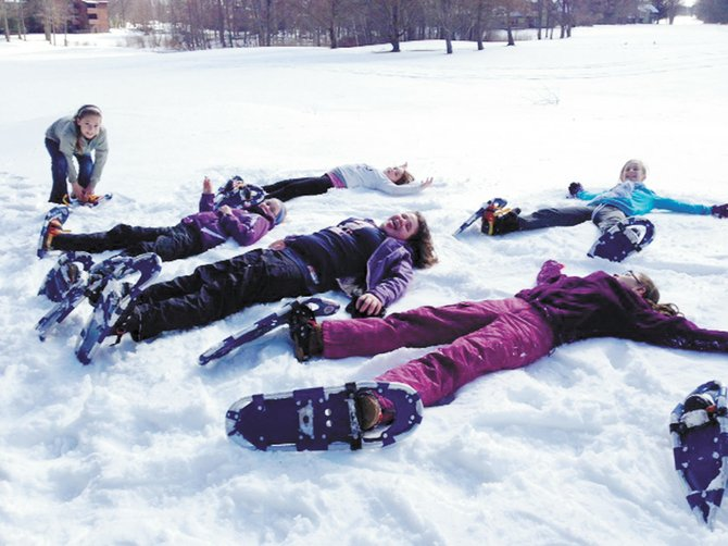 Ray Middle School students take a break from snowshoeing during their physical education class.