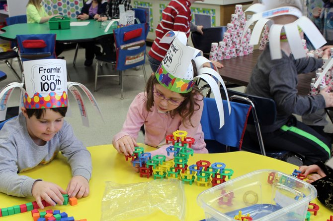 First graders Sebastian Branshaw, left, and Brianne Dzuba work at stacking 100 blocks on the 100th day of school at Reynolds Elementary School.