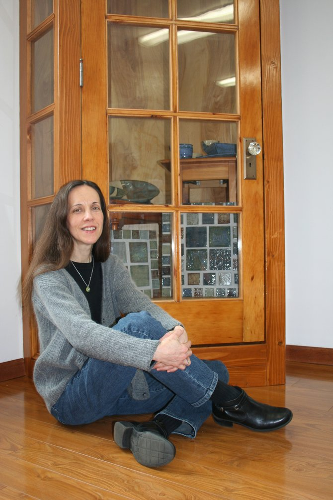 Artist Jenifer Herman sits with the cabinet she made out of the old red door to her grandmother's house.