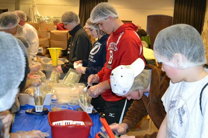 Kevin Carson (red shirt), of Baldwinsville, and his fellow youth group members at St. Mark's Lutheran Church in Baldwinsville help pack meals to be donated Kids Care, An Outreach, Inc., that were distributed to local food pantries in the Syracuse area.