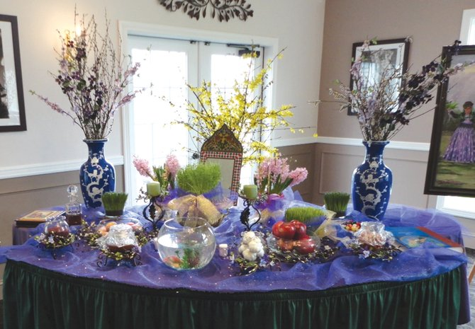 """The Haft-Seen, or Table of Seven S's, from a previous Central New York Persian New Year celebration. The traditional table displays seven items that start with the Persian letter for """"s"""" but can display additional items with special meanings, such as prosperity represented by a bowl of coins."""