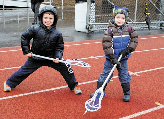 William, right, watches as his brother, Nicholas, gives a Baldwinsville lacrosse player a low five during last Friday's game against Auburn. Prior to the game's start, an announcement was made designating the day William Relyea Day in honor of the 3-year-old who was diagnosed with Stage 3 Neuroblastoma at six months old.