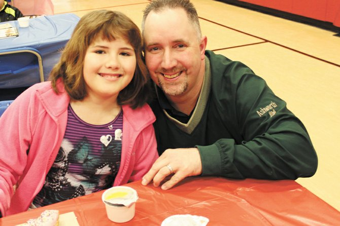 Alexis McCleery brought her father Patrick to school for Elden Elementary School's Dunkin' Donuts for Dudes celebration.