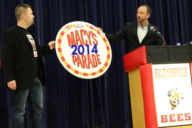 Wesley Whatley, creative director of Macy's Thanksgiving Day Parade, presents marching band director Casey Vanderstouw with the official drum head of the 2014 Macy's Thanksgiving Day Parade.