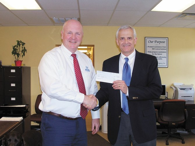 Allstate Insurance agent Christopher Hayden presents Chris Arnold, of Paige's Butterfly Run, with a $1,000 donation from The Allstate Foundation.