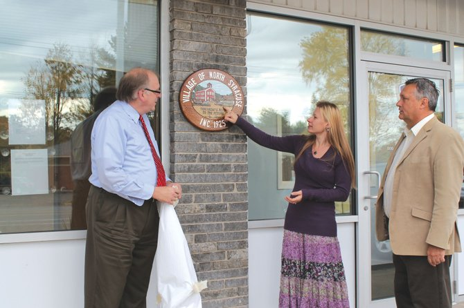North Syracuse Village Justice Robert Bertrand, right, and designer Diane Lewis Ware examine the newly refurbished village seal while Mayor Mark Atkinson looks on. Bertrand's late wife, Debbie, designed the original seal in 1986.