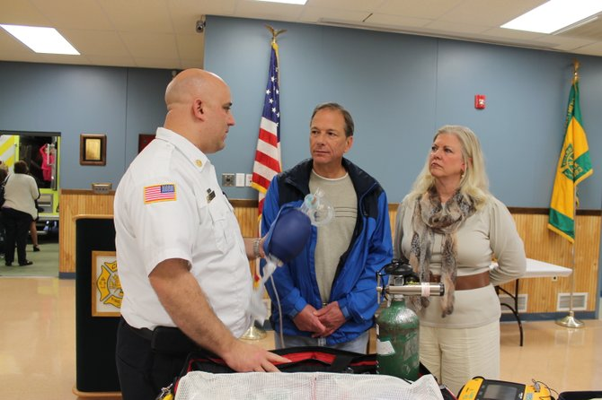 Cicero Volunteer Fire Department Chief Jon Barrett, left, shows some of the department's lifesaving equipment to cardiac arrest victim Kurt Wossner and Ann Cross after an awards ceremony Oct. 19. Wossner was saved by similar equipment by the CFD in February.